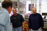 """Walter Taitinfong (left) and Johnny Cofer (right) in front of the Asian Pacific Family Club """"cage"""" at the Oregon State Penitentiary activities floor. Taitinfong is the club's secretary, and Cofer is the garden's project manager."""