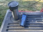 An insulated beverage container and digital thermometer sit on the tailgate of a pickup truck.