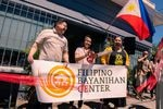 """Celebrants cut a red ribbon at the grand opening of Portland's Filipino Bayanihan Center in June 2021. Three people are pictured in front of a small building holding a banner that reads """"FILIPINO BAYANIHAN CENTER."""" Behind them hangs a Filipino flag. One woman holds large scissors which she's just used to cut a red ribbon across the front of the building's entrance."""