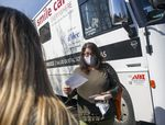 A person stands outside a large bus or RV wearing a mask and holding paperwork.