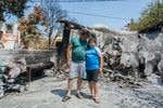 """Stathis Steffos hugs his 11-year-old son, Kostas, outside their burned home in the village of Rovies. Kostas used a makeshift broom to help his father beat back flames as they rescued the family sheep. """"But he cried when he saw what was happening to us,"""" Stathis Steffos says of his son. """"He saw it firsthand."""""""