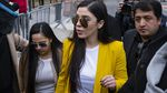A woman in a bright yellow jacket and sunglasses is in focus at the center of a group of people.