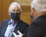 Two people wearing suits and masks talk inside the Oregon state Capitol building.