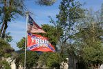 Flags in a Prineville yard combine the text of the 2nd Amendment, Confederate imagery, and political support for former President Donald Trump. The house next door has a for sale sign up on May 17, 2021.