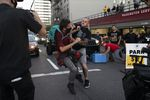 A Trump cruise rally demonstrator punches another person as the caravan moves through downtown Portland, Ore., Aug. 30, 2020.