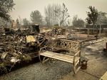 A charred bench at a park where a wildfire burned.