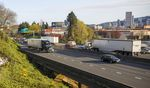 Vehicles drive on a divided highway, while tall buildings from downtown Portland can be seen in the distance.