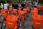 rows of orange BIKETOWN bikes are lined up in front of a crowd of people