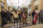 In this Wednesday, Jan. 6, 2021 file photo supporters of President Donald Trump are confronted by U.S. Capitol Police officers outside the Senate Chamber inside the Capitol in Washington. Jacob Anthony Chansley, the Arizona man with the painted face and wearing a horned, fur hat, was taken into custody Saturday, Jan. 9, 2021 and charged with counts that include violent entry and disorderly conduct on Capitol grounds.