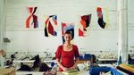Britt Howard, the founder and owner of the Portland Garment Factory, pictured in her workspace.  She's standing with folded fabrics on a big table. Behind and around her are tools and sewing materials, some at smaller workstations in the background. Brightly colored fabric art hangs on a white wall behind her like flags.