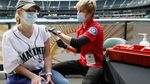 A person receives a vaccine injection inside a large baseball stadium.