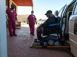 A person in an electronic wheelchair uses a ramp to exit a van onto a brick sidewalk outside a building, while two people wearing health care scrubs look on.