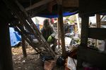 """Jose Ortiz pauses, Monday, Dec. 7, 2020, at the ladder to the residence he built in the homeless encampment known as the Jungle in Ithaca, N.Y. When Ortiz tested positive for COVID-19 last month, he was able to isolate at his elaborately crafted shelter, which includes a """"treehouse"""" about waist-high with a wood stove pipe and a tree protruding from the tarp-covered top."""