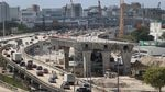 Cars fill an elevated highway, while a large crane looms over construction of an even higher-up freeway ramp that is not yet complete.