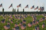 Activists from the COVID Memorial Project mark the deaths of 200,000 lives lost in the U.S. to COVID-19 after placing thousands of small American flags on the grounds of the National Mall in Washington, Tuesday, Sept. 22, 2020.