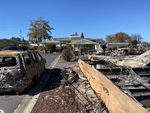 On October 14 — more than a month after the Almeda Fire — burned-out cars and other hazardous debris remained in front of Misty Muñoz's house at Medford Estates.