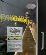 """Ezra Caraeff, one of the owners of Paydirt, a bar in Northeast Portland, papers the windows of the bar on Wednesday, Nov. 18, 2020. The bar will close for at least the next four weeks, part of Oregon's """"freeze"""" and effort to slow the spread of COVID-19."""