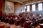 People sit at desks on the floor of the Oregon Senate in the state Capitol building.