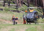 Searchers exit a Brim helicopter after finding 69-year-old Harry Burleigh alive on Sunday, May 23, 2021.