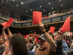 Members of the audience express dissent through red cards at the Portland Mayoral Candidate Debate.