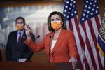 A masked Nancy Pelosi addresses the media from a lectern in the Capitol as a masked Blumenthal looks on from over her right shoulder. American flags hang in the background.