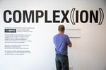 Dan Ling hangs a bracket for the Be Nice (White) You're In Bend exhibit at Scalehouse in Bend, Ore., Friday, Aug. 6, 2021.