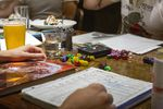 Players at set up for a game of Dungeons & Dragons with dice sets, player sheets and player handbooks. The game uses various dice rolls to move the story forward and determine if an action succeeds or fails.