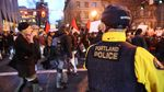 Portland police watch the crowd of demonstrators as they march through the city's downtown on Jan. 20, 2017.