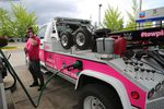 A tow truck driver stands outside next to their truck and talks on a cell phone while the truck is filled with gasoline.