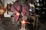 Darryl Nelson uses techniques of his trade handed down generations. At his anvil, he works a piece of heated steel with hammer and chisel, tools he made himself.