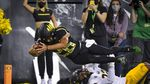 Oregon running back Travis Dye dives into the end zone over California safety Daniel Scott.