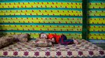 Adnan, 3, naps in his family's newly decorated caravan in the Zaatari camp for Syrian refugees in Jordan in August 2015. After living in a tent for two years, being able to decorate their caravan, essentially a metal box, gives his family a sense of home and comfort. They expected to stay in Jordan for at the most two months, thinking the conflict would not last much longer after they arrived in Jordan. As of April 2017, Adnan has spent four of his five years in the refugee camp.