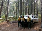 Firefighters with Methow River Wildfire worked to protect buildings during the Crescent Mountain Fire. Engine boss Steven Baltrusch (right) also works various jobs during the off season. Also pictured: Allen Dolph and Richie Harvey.