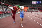 Gold medalist Mutaz Barshim, left, of Qatar and silver medalist Gianmarco Tamberi of Italy celebrate on the track after the final of the men's high jump at the 2020 Summer Olympics, Sunday, Aug. 1, 2021, in Tokyo, Japan.
