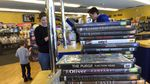 A stack of DVDs sits on a counter, while an adult and a child in the background check out at a register and a clerk stares at a computer.