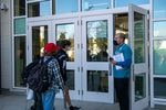 Students approach a door while an adult stands outside wearing a mask and holding a radio and a clipboard.