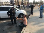 A man involved in the brawl recovers from mace as police stand by in Bend, Oct. 3, 2020.
