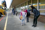A student touches elbows with a teacher as she leaves hybrid school at Ellsworth Elementary School in Vancouver, Wash., March 1, 2021. This week, students in Oregon and Southwest Washington are returning to school, and now it's in-person, full time.