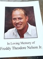 """A picture of a paper funeral program. The program features the smiling image of a man and the words """"In Loving Memory of Freddy Theodore Nelson Jr."""""""