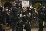Paint covers Portland officers policing protests in downtown Portland, Ore., Aug. 12, 2020.