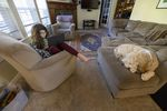 Mina Mohandessi, left, completes her virtual schoolwork as her dog Watson rests nearby, at their home in Vancouver, Wash., March 12, 2021.