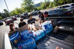 Members of the Social Club stack supplies to distribute to demonstrators in Happy Valley, Ore., Wednesday, June 3, 2020.