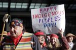 A sign is held aloft during an Indigenous Peoples Day march Monday, Oct. 9, 2017, in Seattle. In 2014, the Seattle City Council voted to stop recognizing Columbus Day and instead turned the second Monday in October into a day of recognition of Native American cultures and peoples.