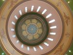 Light enters narrow windows surrounding a floral motif on the ceiling of the Oregon Capitol building.