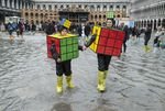 A mother and son wearing Rubik's Cube costumes walk in flooded Saint Mark's Square on the last day of Carnival on March 4, 2014, in Venice, Italy.