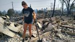 Madeline Smith walks between what was the living room and laundry room of her house in Talent, Ore., south of Medford. She has been picking through the rubble looking for anything that can be salvaged after wildfire tore through her home.