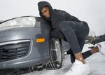 Food delivery driver Nalik Jackson of Portland struggles to put on snow chains in Beaverton. This was Jackson's first time putting chains on a car so he consulted YouTube to learn how.