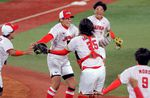Japan's pitcher Yukiko Ueno, 2nd left, and catcher Haruka Agatsuma, center, celebrate their gold medal victory as other teammates run to join on July 27, 2021.