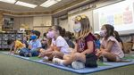 Children sit on a mat together while wearing face coverings.