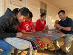 Cinthya, David, Laura and Francisco Bautista put finishing touches on a hand woven tapestry.